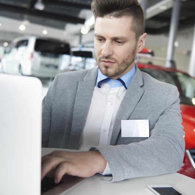"""Waist up of salesman working on laptop"" stock image"