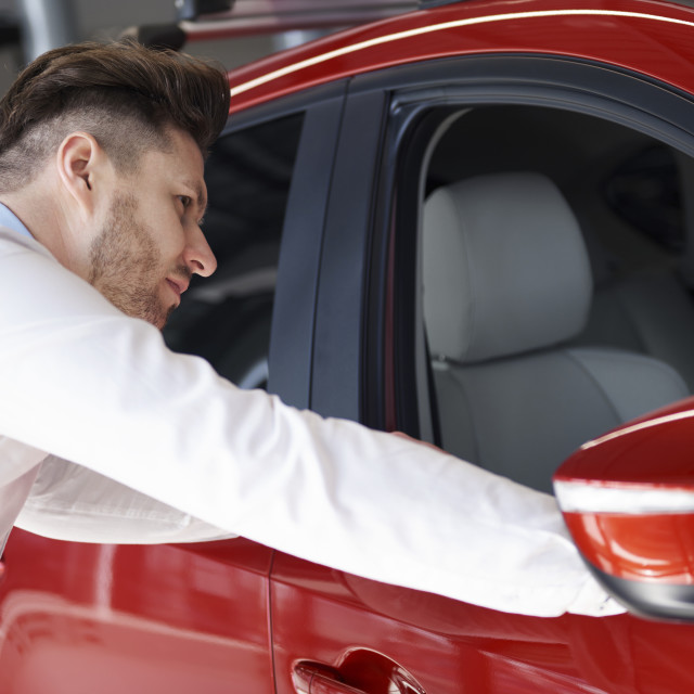 """""""Side view of man next to red car in showroom"""" stock image"""