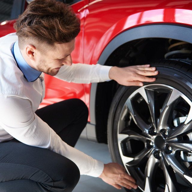 """""""Salesman checking the shiny rims in new car"""" stock image"""