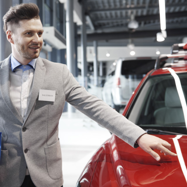 """""""Handsome salesman talking about car values"""" stock image"""