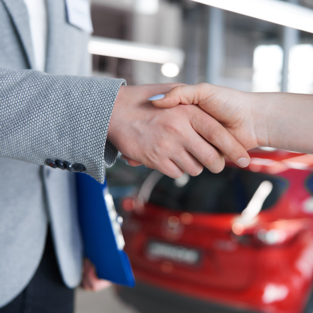 """""""Woman shaking hands with salesman in the showroom"""" stock image"""