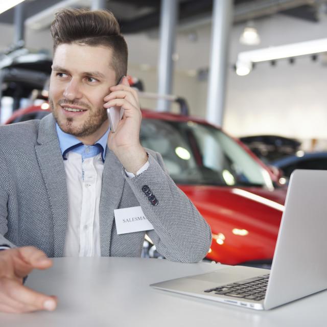 """Close up of multi tasking salesman"" stock image"