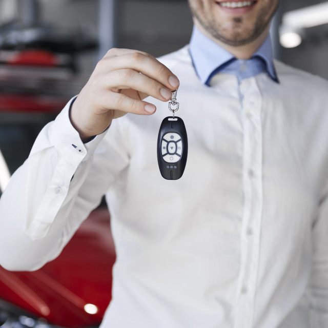"""""""Salesman holding out car key in showroom"""" stock image"""