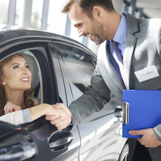 """""""Car dealer making deal with female customer"""" stock image"""