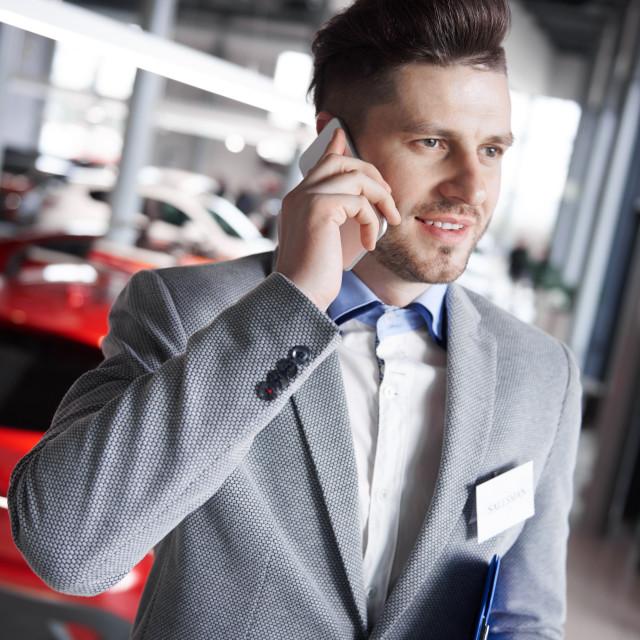 """Car dealer having a call over work"" stock image"