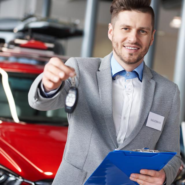 """Smiling salesman handing car keys"" stock image"
