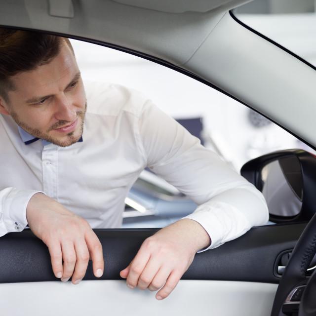 """Pensive man looking at dashboard"" stock image"