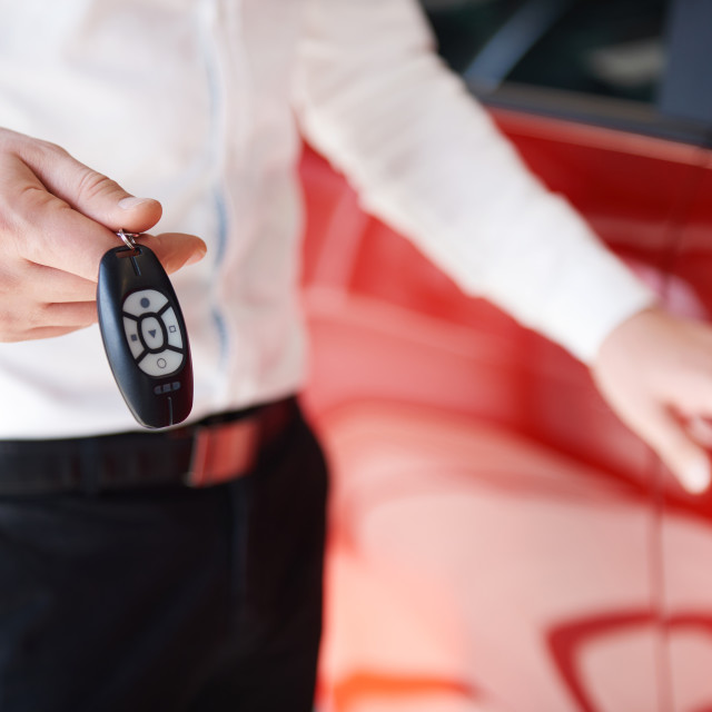"""""""Man holding keys to brand new car in showroom"""" stock image"""