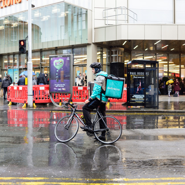 """Deliveroo rider in the rain ."" stock image"