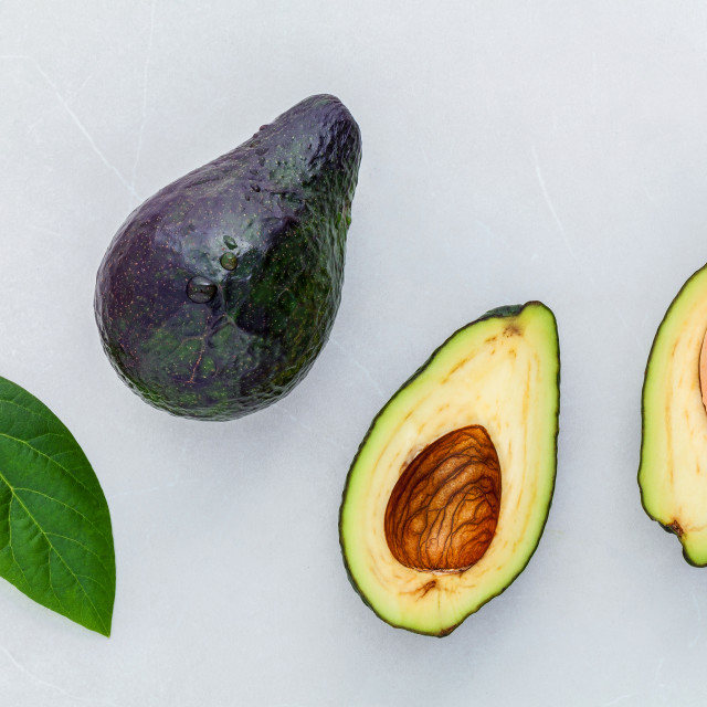 """Close up fresh afresh avocado and avocado leaves on marble background flat..."" stock image"