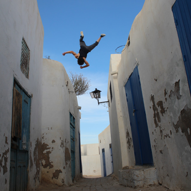 """Taher nagati doing a side flip between buildings"" stock image"