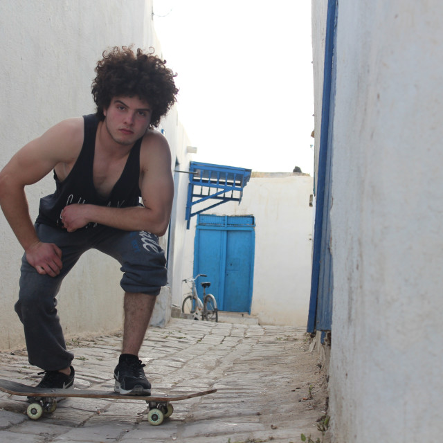 """Taher Nagati posing with his skateboard"" stock image"