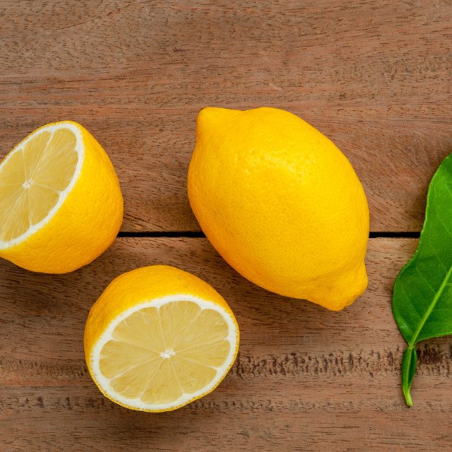 """Fresh lemons and lemons leaves on rustic wooden background. Fresh lemons and..."" stock image"