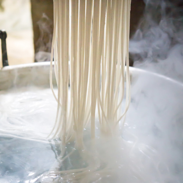 """""""Traditional noodles making on a vintage machine"""" stock image"""
