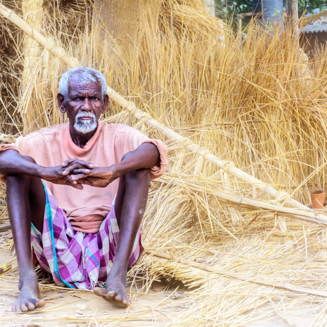 """An old tribal man sitting infront of haystack with copy space"" stock image"