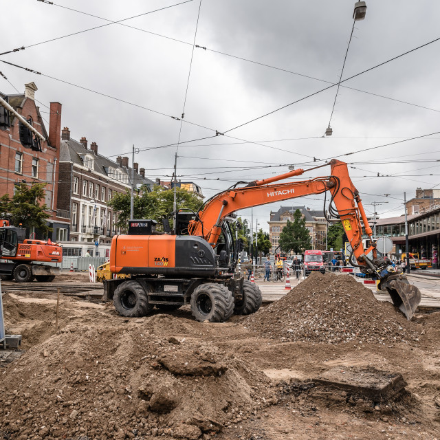 """""""Amsterdam, Netherlands - August 3, 2016: Backhoe machine repairing the tram tracks in the streets of Amsterdam a cloudy and rainy day"""" stock image"""