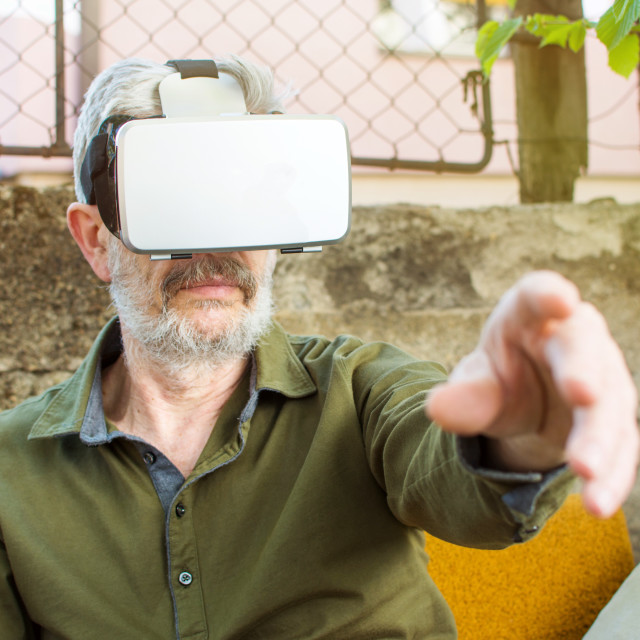 """Senior man using virtual reality in backyard"" stock image"