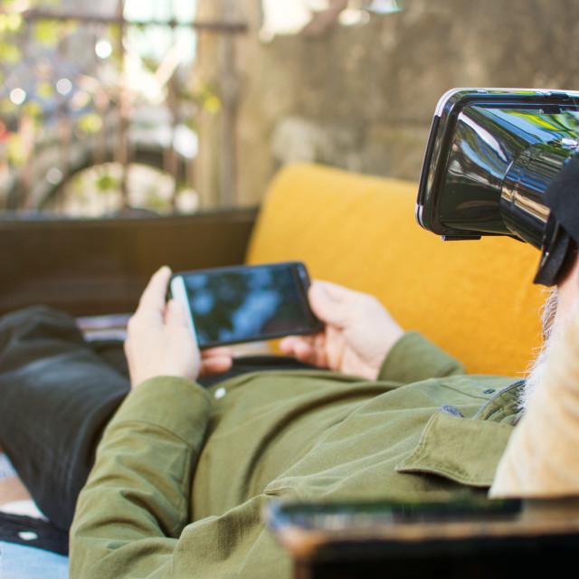 """Senior man using virtual reality on a sofa bed"" stock image"