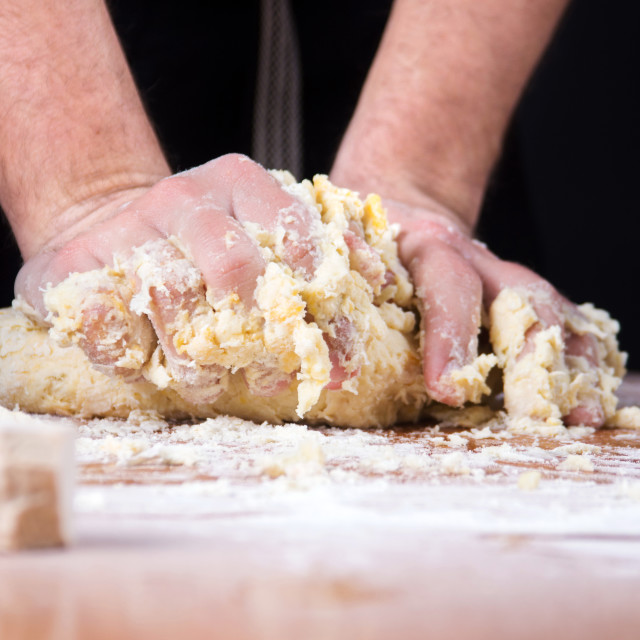 """Male baker kneading dough on flour covered table"" stock image"