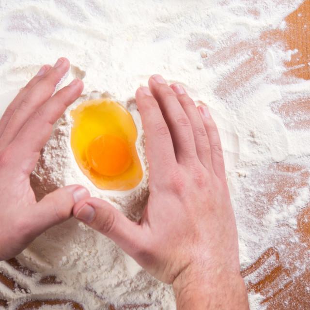 """Male hands around broken egg on flour"" stock image"