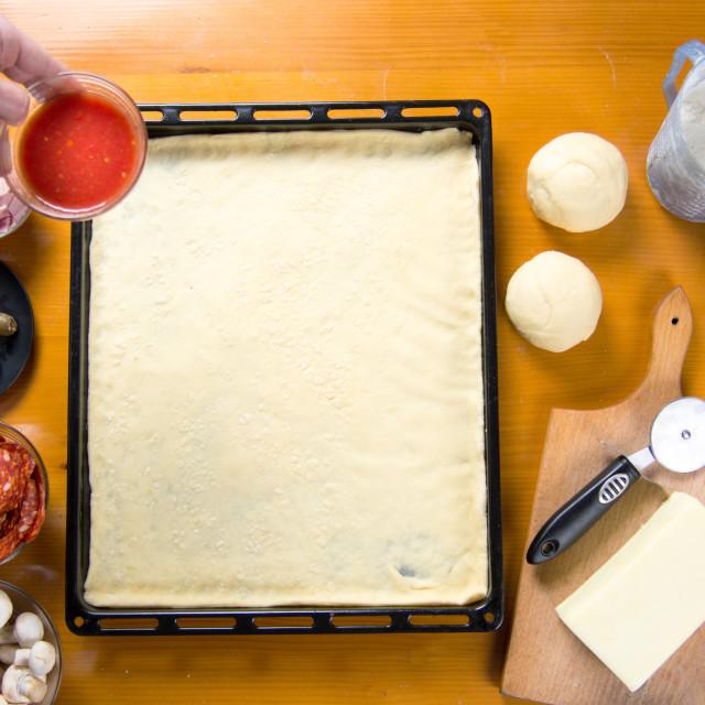 """Man putting tomato sauce on pizza base"" stock image"