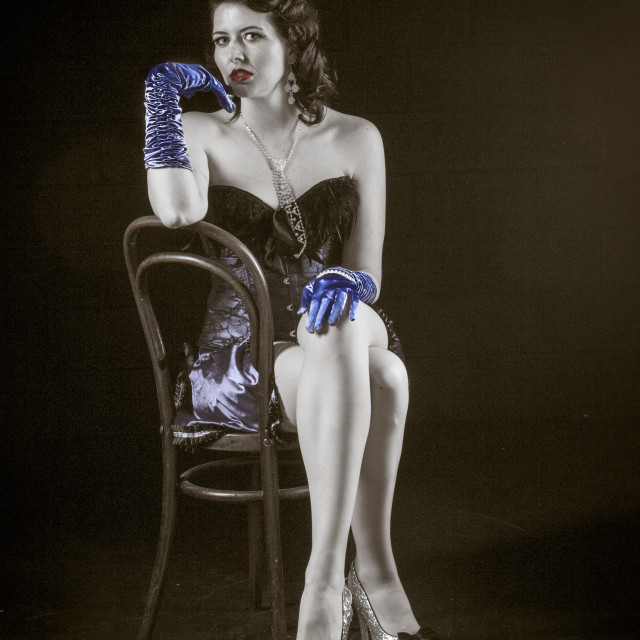 """Burlesque model on chair with blue gloves"" stock image"