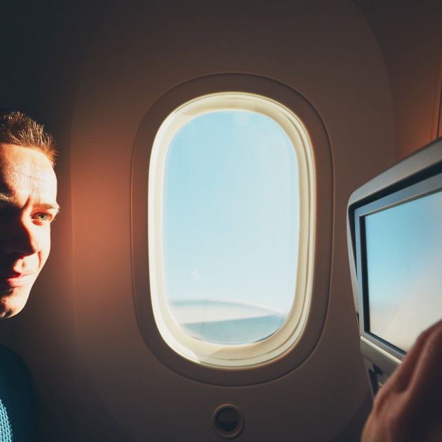 """Comfortable traveling by airplane. Young passenger enjoying his journey inside an airplane."" stock image"