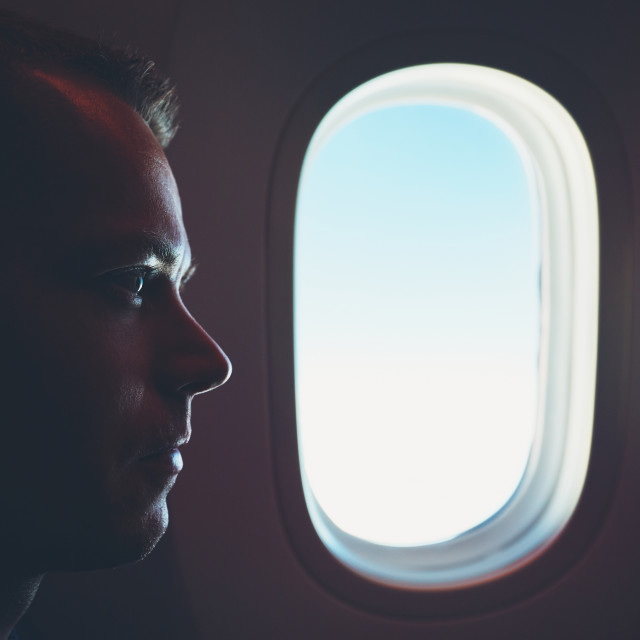 """Comfortable traveling by airplane. Silhouette of the passenger enjoying his journey inside an airplane."" stock image"
