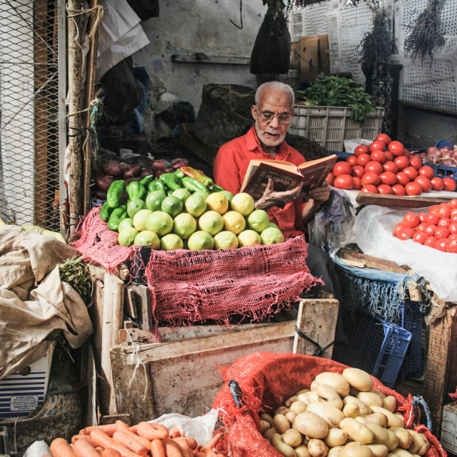 """Old man reading book at the market"" stock image"