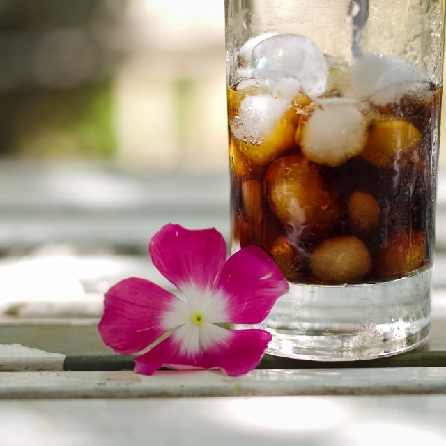 """Lovely pink flower beside a Glass of Ice coffee"" stock image"