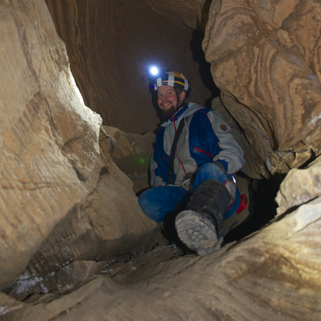 """Man caving with headlamp on"" stock image"