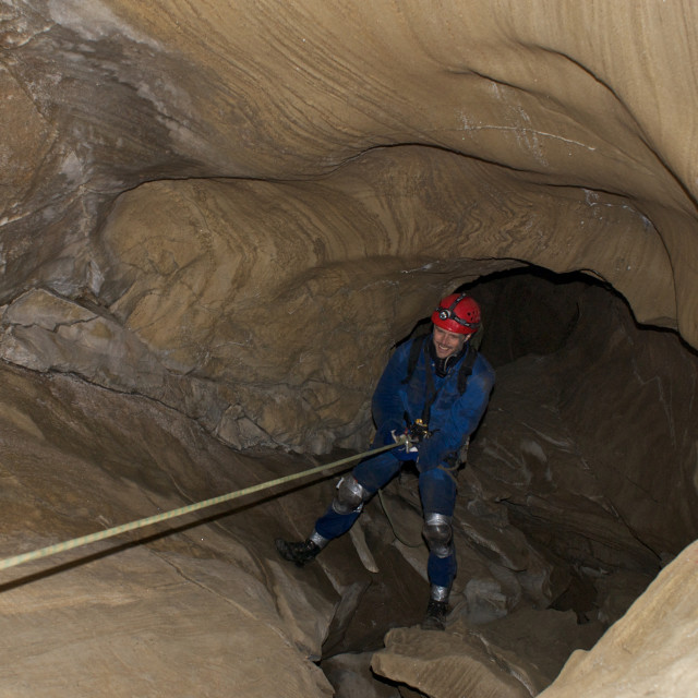 """""""Man rapelling in cave."""" stock image"""