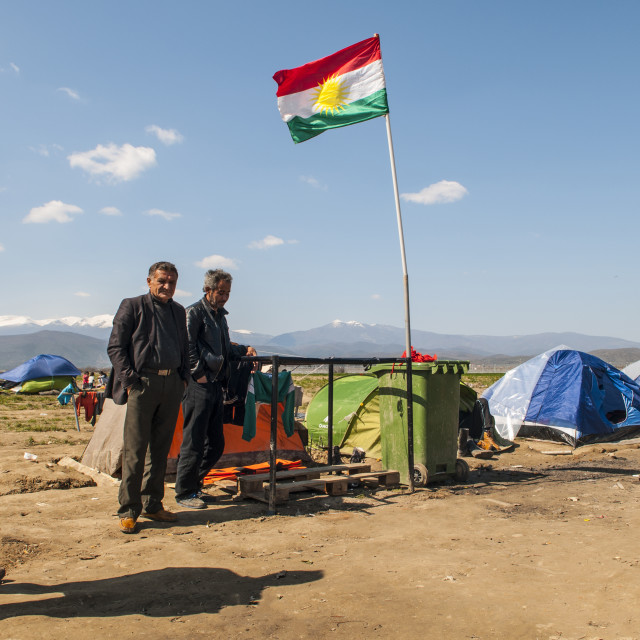 """Kurdish refugees with their flag in the field of diomeni refugees in Greece"" stock image"
