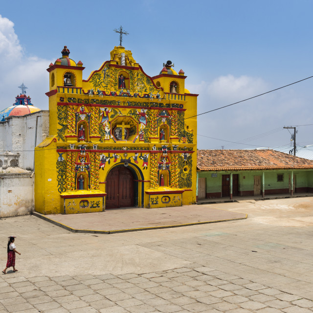 """The colorful church of San Andres Xecul and three local Mayan woman walking on the street in Guatemala"" stock image"