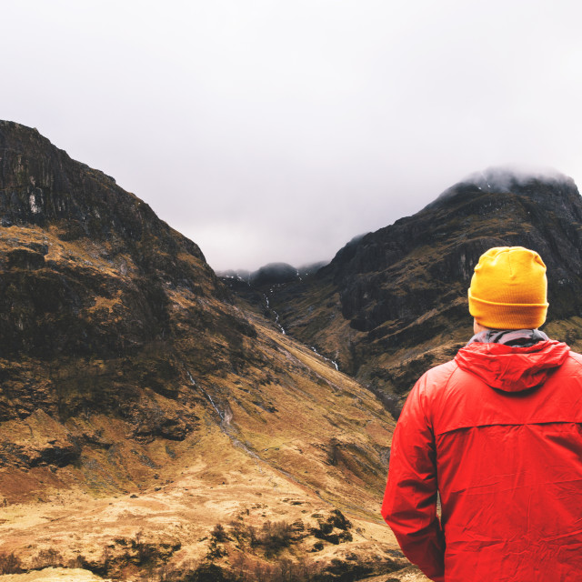 """Man standing in cloudy mountains in Glencoe, Scotland."" stock image"