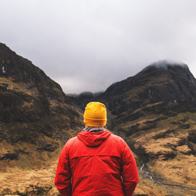 """Man standing in mountains in Glencoe, Scotland."" stock image"