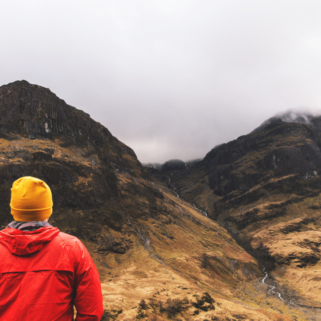 """Man walking in mountains in Glencoe, Scotland."" stock image"