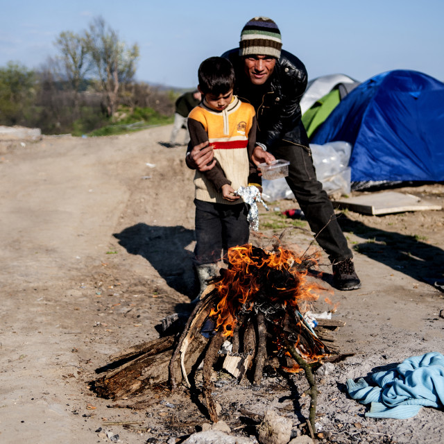 """a father with his son light a fire in the field of Idomeni refugees on the border between Greece and Macedonia"" stock image"