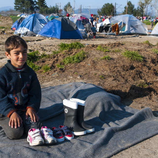 """a child sells rubber boots in the refugee camp in Idomeni inn Greece"" stock image"