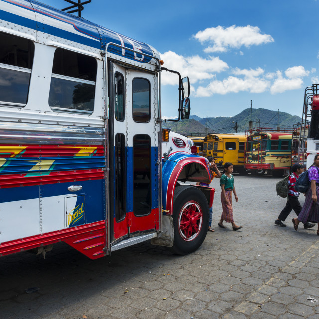 """Family in a bus terminal with colorful buses in Antigua, Guatemala"" stock image"