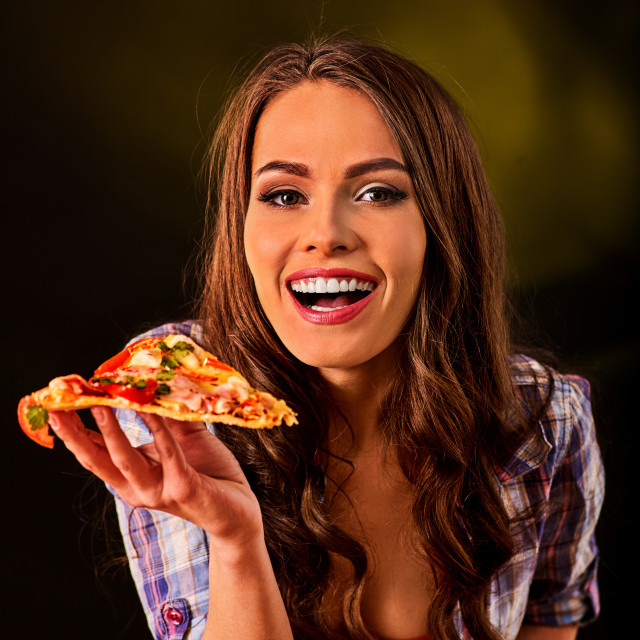 """Woman eating slice of Italian pizza . Student consume fast food."" stock image"
