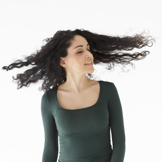 """Brunette girl shaking her hair on white background"" stock image"