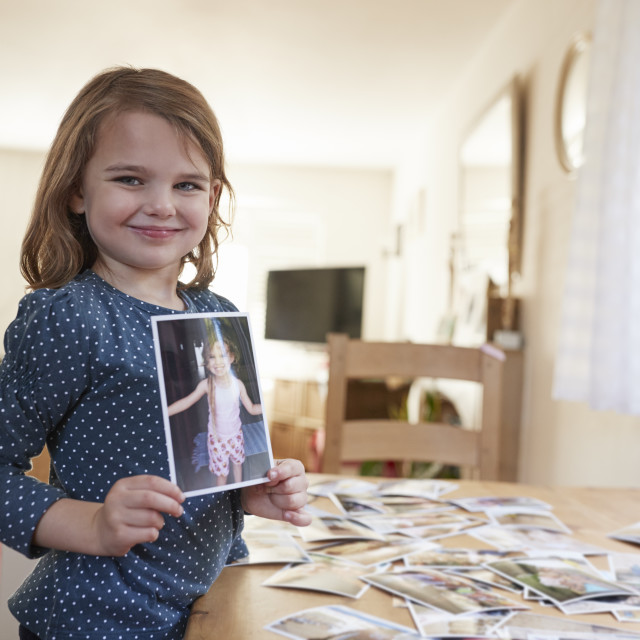 """Young Girl Looking At Family Photographs On Table At Home"" stock image"