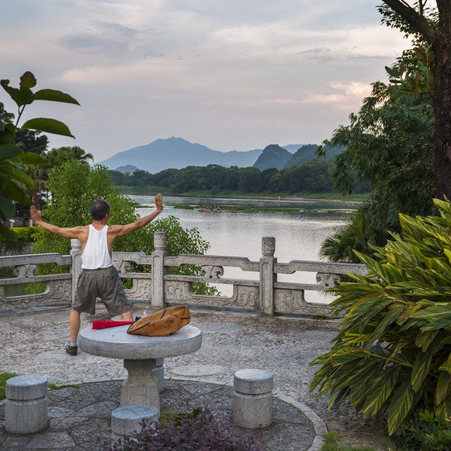"""""""Guilin, China - July 31, 2012: Man practicing Tai chi in the banks of the Li River in Guilin, China."""" stock image"""