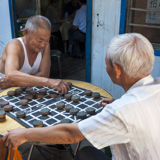 """Dunhuang, China - August 7, 2012: Two Chinese man playing Chinese Chess (Xiangqi) in a street of the city of Dunhuang, China"" stock image"