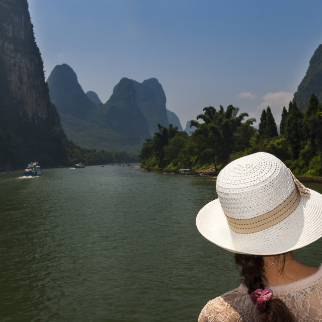 """""""Woman with a hat looking at the landscape in a river cruise in the Li River between Guilin and Yangshuo, in China; Concept for travel in China"""" stock image"""