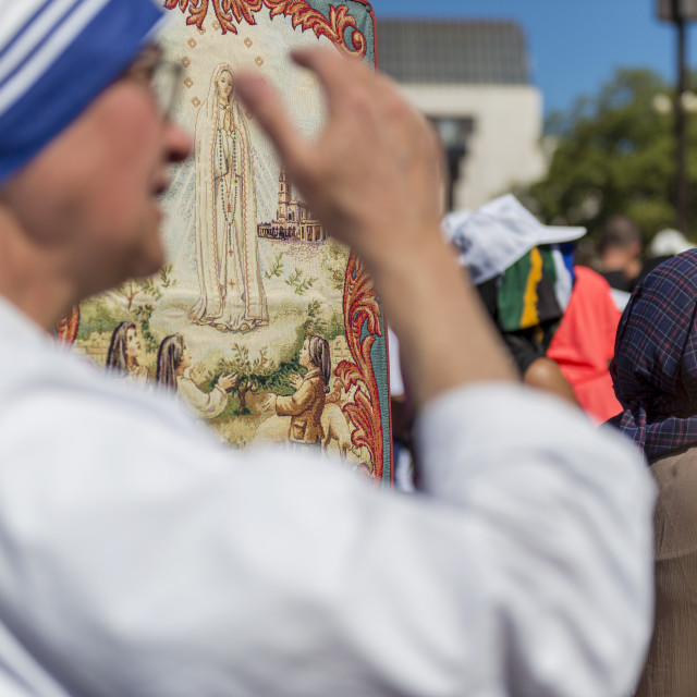 """""""Fatima, Portugal - May 13, 2014: Blurred silhouette of a nun with the figure of the Virgin Mary on the background at the Sanctuary of Fatima during the celebrations of the apparition of the Virgin Mary in Fatima, Portugal."""" stock image"""
