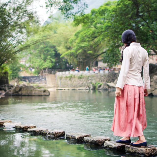"""Girl walking on the stone bridge in the river"" stock image"