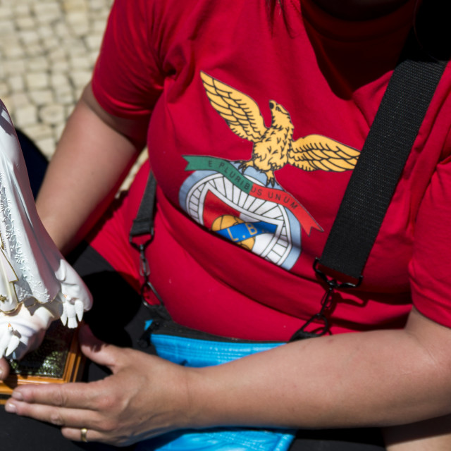 """""""Fatima, Portugal - May 13, 2014: Woman holding a small statue of the Virgin Mary and wearing a Benfica shirt at the Sanctuary of Fatima during the celebrations of the apparition of the Virgin Mary in Fatima, Portugal."""" stock image"""