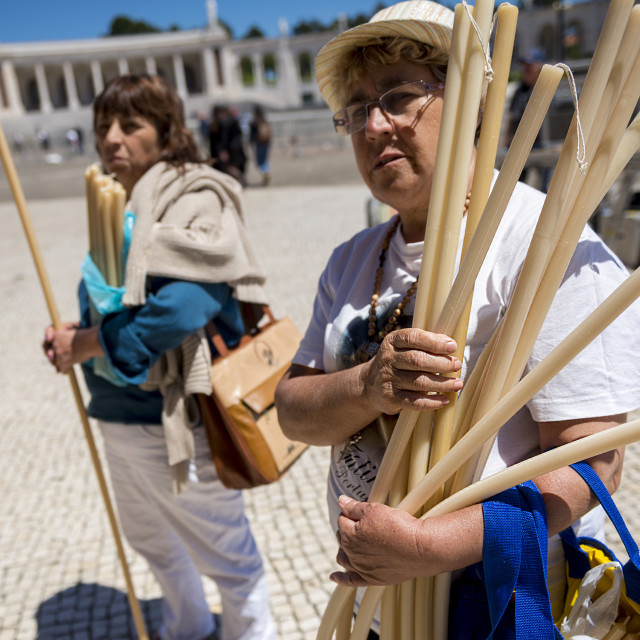 """""""Fatima, Portugal - May 13, 2014: Woman holding candles to pay a promise at the Sanctuary of Fatima during the celebrations of the apparition of the Virgin Mary in Fatima, Portugal."""" stock image"""